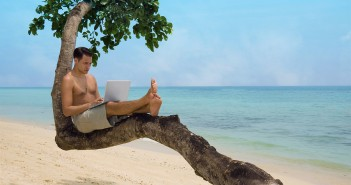 man on laptop at beach