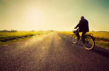 Old man riding a bike on asphalt road towards the sunny sunset s