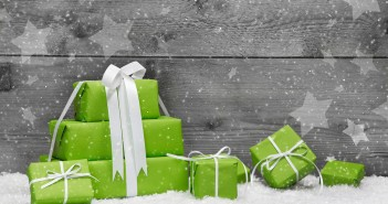 Green Christmas presents with snow on grey wooden background for