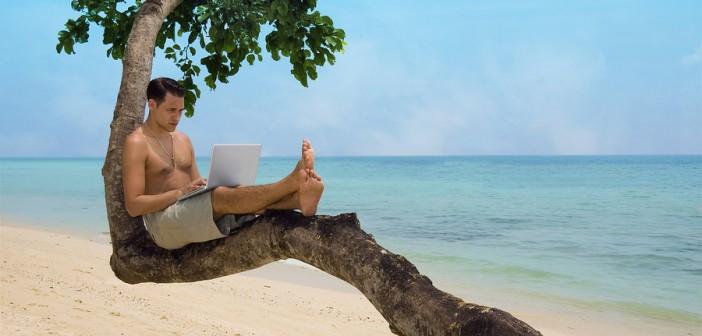 man on laptop at beach