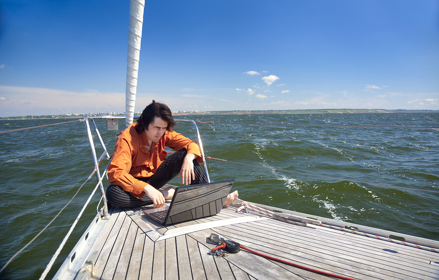 man writing e-newsletters on laptop on boat
