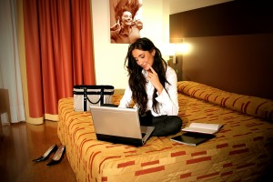 writer working on laptop on bed writing articles