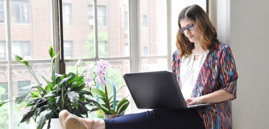 woman sitting on window ledge using laptop