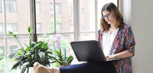 woman sitting on window ledge using laptop