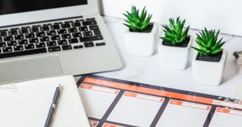 laptop with day planner on desk