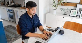 man working on laptop with camera on table