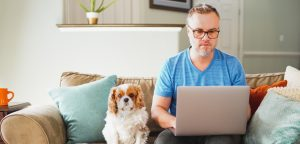 man working on laptop with dog on couch