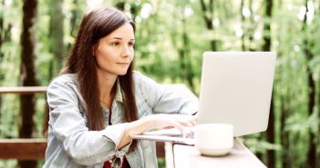 woman working on laptop on porch