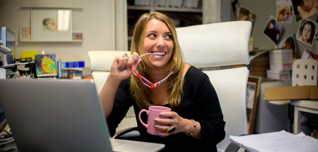 woman by computer smiling finding niche