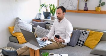 man working on computer at home couch