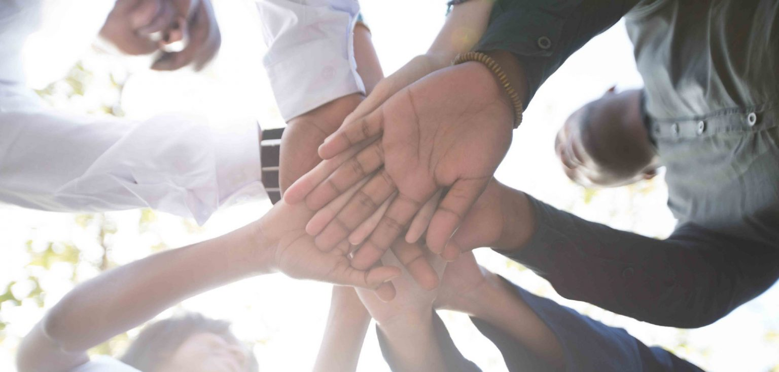 people holding their hands together to help