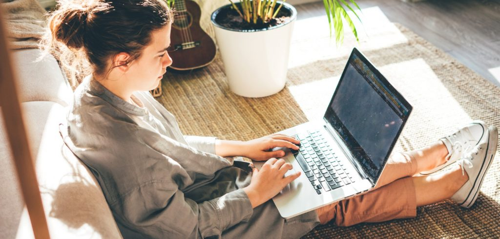 woman writing first draft on laptop in living room