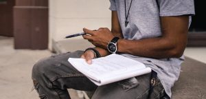 man writing in his authentic voice on a paper pad